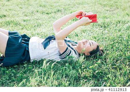 芝生に寝転がって本を読む高校生 41112913