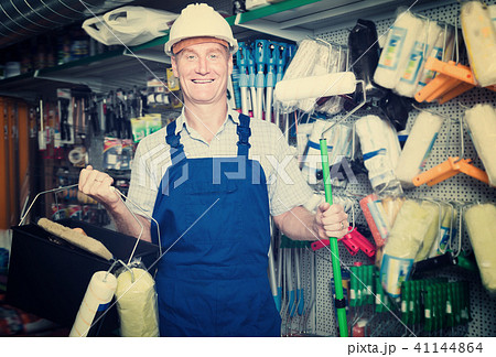 Portrait of adult workman choosing soft roller 41144864