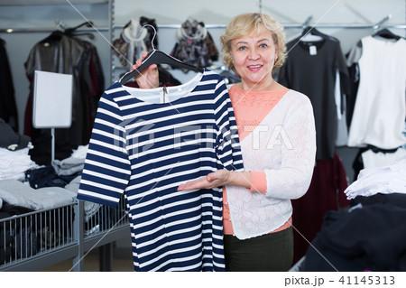 Nice woman consumer choosing striped dress 41145313