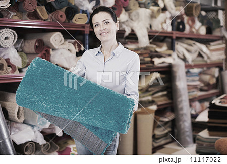 Female touching and choosing carpets 41147022