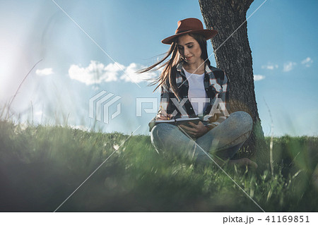 Beautiful girl with pen and notebook on fresh air 41169851