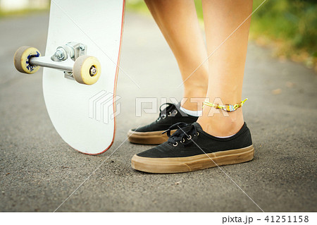 view of the legs of a girl with a skateboard on the street 41251158