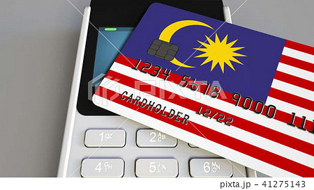 Payment or POS terminal with credit card featuring flag of Malaysia. Malaysian retail commerce or 41275143