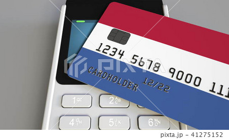 Payment or POS terminal with credit card featuring flag of the Netherlands. Dutch retail commerce or 41275152