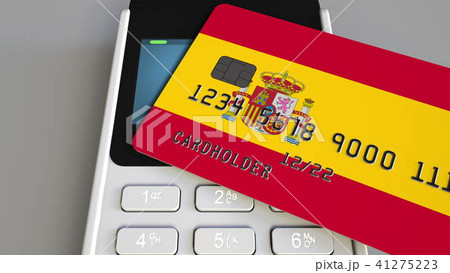 Payment or POS terminal with credit card featuring flag of Spain. Spanish retail commerce or banking 41275223