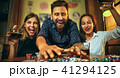 Side view photo of friends sitting at wooden table. Friends having fun while playing board game. 41294125