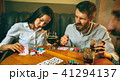 Side view photo of friends sitting at wooden table. Friends having fun while playing board game. 41294137