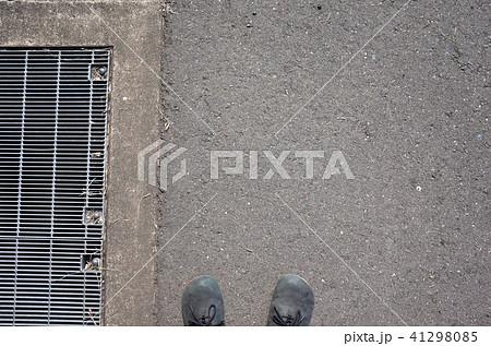 グレーチングとアスファルトと靴、道路を歩く 41298085
