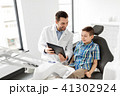 dentist showing tablet pc to kid patient at clinic 41302924