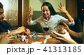 Side view photo of friends sitting at wooden table. Friends having fun while playing board game. 41313185