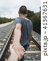 men holding hands on the railroad tracks 41367631