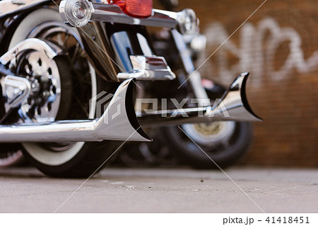 Shiny chromed retro fishtail exhausted pipes of luxury motorcycle. Brick wall with defocused 41418451