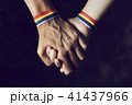 men holding hands with rainbow-patterned wristband 41437966