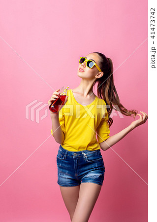 Smiling teenage girl standing and drinking beverage through straw 41473742