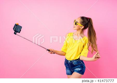 Smiling teenage girl making selfie with stick 41473777