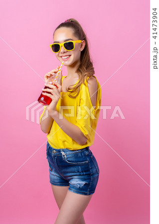 Smiling teenage girl standing and drinking beverage through straw 41473904