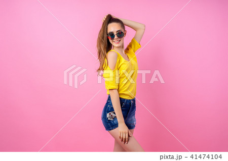 Happy teenage girl standing with flying hair 41474104