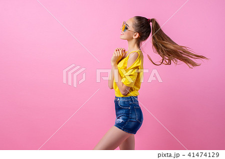 Happy teenage girl standing with flying hair 41474129