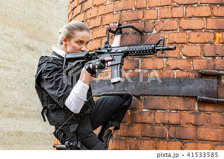 powerful woman holding gun war action movie styleの写真素材