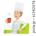 コックコートを着用した年配の料理人がソファーに座ってコーヒーを飲んでいる 41562078