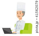 コックコートを着用した年配の料理人がソファーに座ってノートパソコンを操作している 41562079
