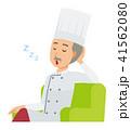 コックコートを着用した年配の料理人がソファーに座って居眠りをしている 41562080