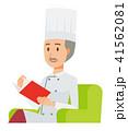 コックコートを着用した年配の料理人がソファーに座って読書をしている 41562081