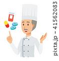 コックコートを着用した年配の料理人が医薬品について説明している 41562083