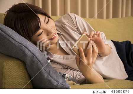 寝転んでスマホを見る若い女性 41609875