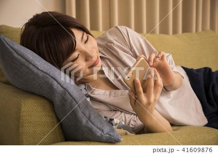 寝転んでスマホを見る若い女性 41609876
