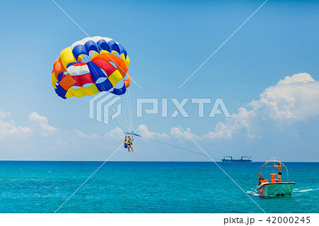 Couple of tourists flying on a colorful parachute 42000245