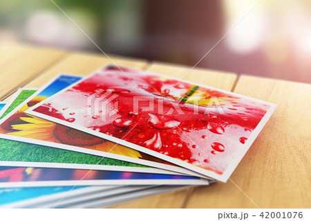 Stack color photo pictures on wooden table outdoor 42001076