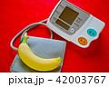 デジタル血圧計とバナナ 赤バック 42003767