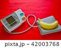デジタル血圧計とバナナ 赤バック 42003768