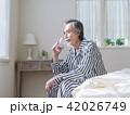 ベッドに座って水を飲むシニア男性 42026749