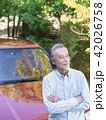 車にもたれる笑顔のシニア男性 42026758