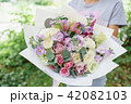 Beautiful summer bouquet. Arrangement with mix flowers. Young girl holding a flower bunch . The 42082103
