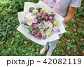 Beautiful summer bouquet. Arrangement with mix flowers. Young girl holding a flower bunch . The 42082119
