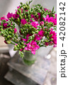 bright pink freesia flowers in glass vase on wooden table. Beautiful summer bouquet. Arrangement 42082142