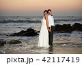 Groom and bride stand in sea water 42117419