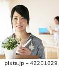 じょうろを持ち微笑む女性 42201629