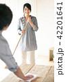 ほうきで掃除をする女性とテーブルを拭く男性 42201641