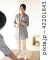 ほうきで掃除をする女性とテーブルを拭く男性 42201643