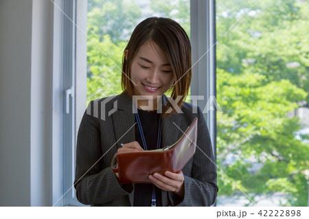 手帳に書き込むスーツの女性 42222898