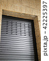Brick wall building with black metal door 42225397