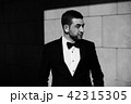 Handsome confident bearded businessman in suit posing at the squared textured wall. Black and white 42315305