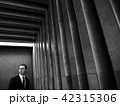 Handsome confident bearded businessman in suit posing at the striped textured wall. Black and white 42315306