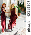 Two beautiful girls in red bridesmaid dresses walking on the streets of old european town 42315308