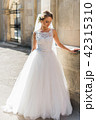 Elegant emotional brunette bride in stylish white dress posing in the old lviv street 42315310