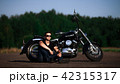 Handsome biker man in glasses sitting at his motorcycle. Countryside road background 42315317